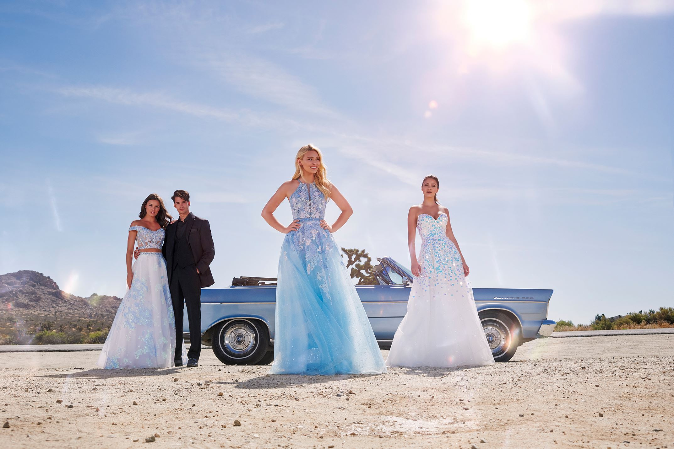 Models in Ellie Wilde dresses in front of a car in the desert