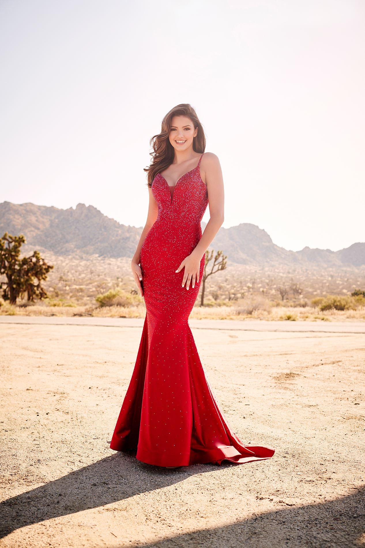 Brunette model in long red prom dress in desert