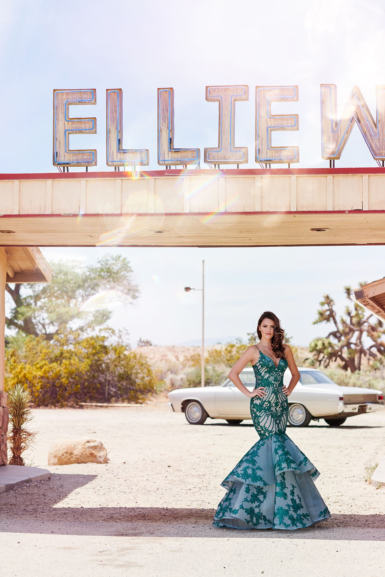 Brunette model in long green prom dress by Ellie Wilde