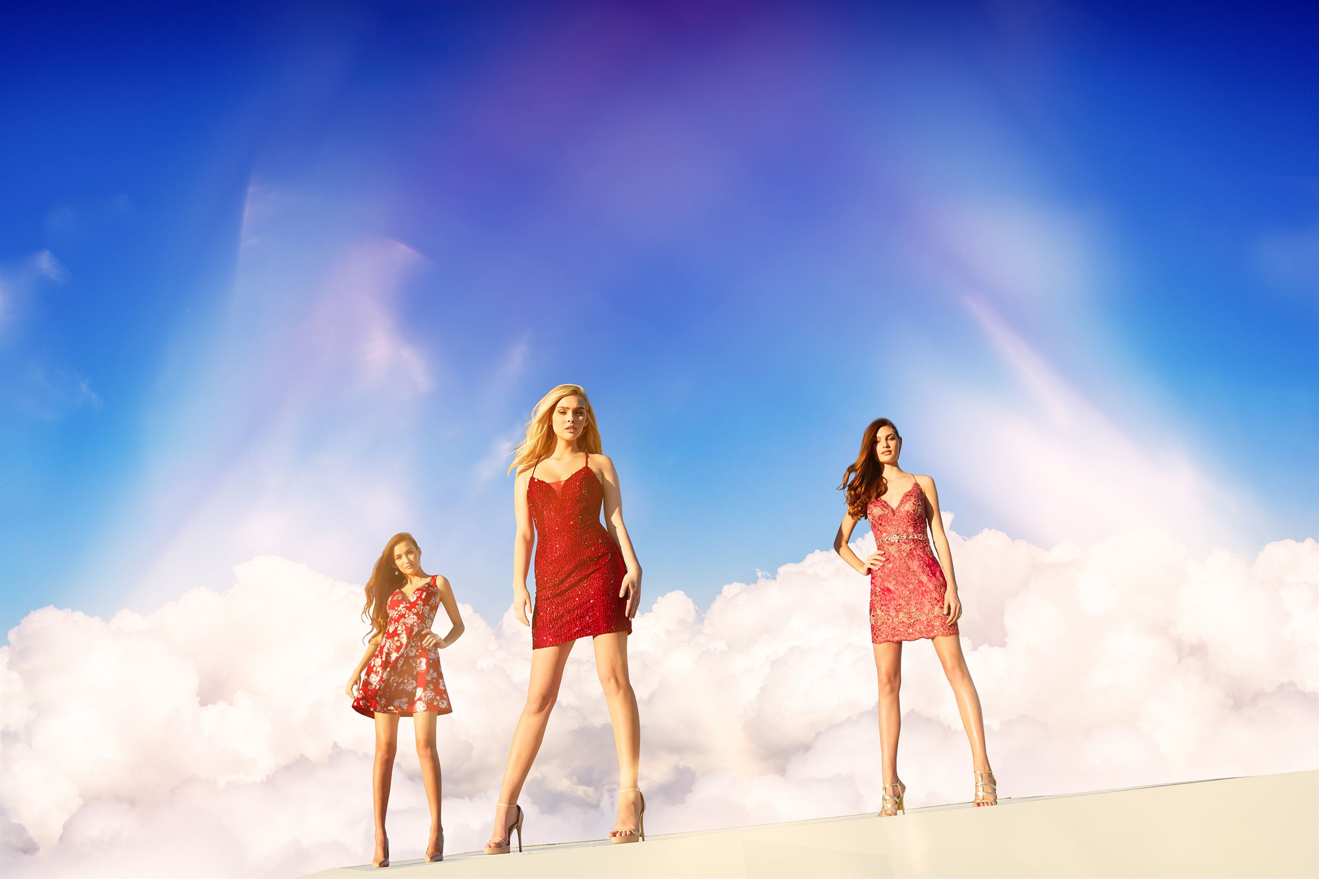 Models in short homecoming dresses in front of clouds