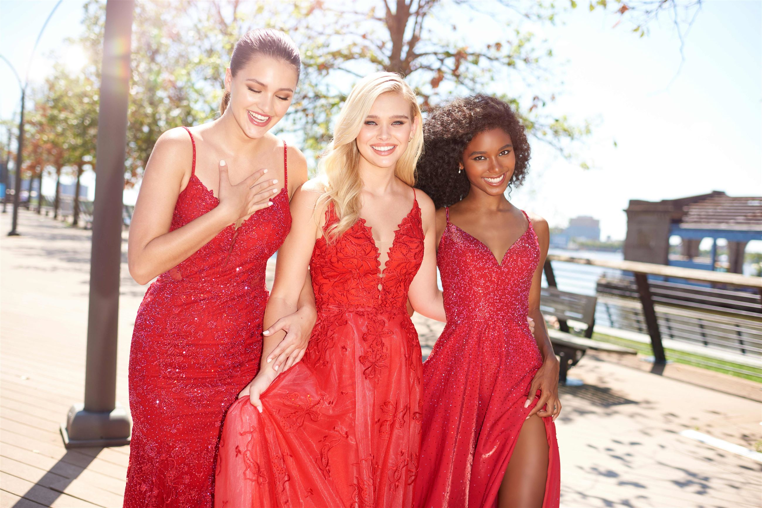3 girls smiling and walking down the street in red Ellie Wilde prom dresses