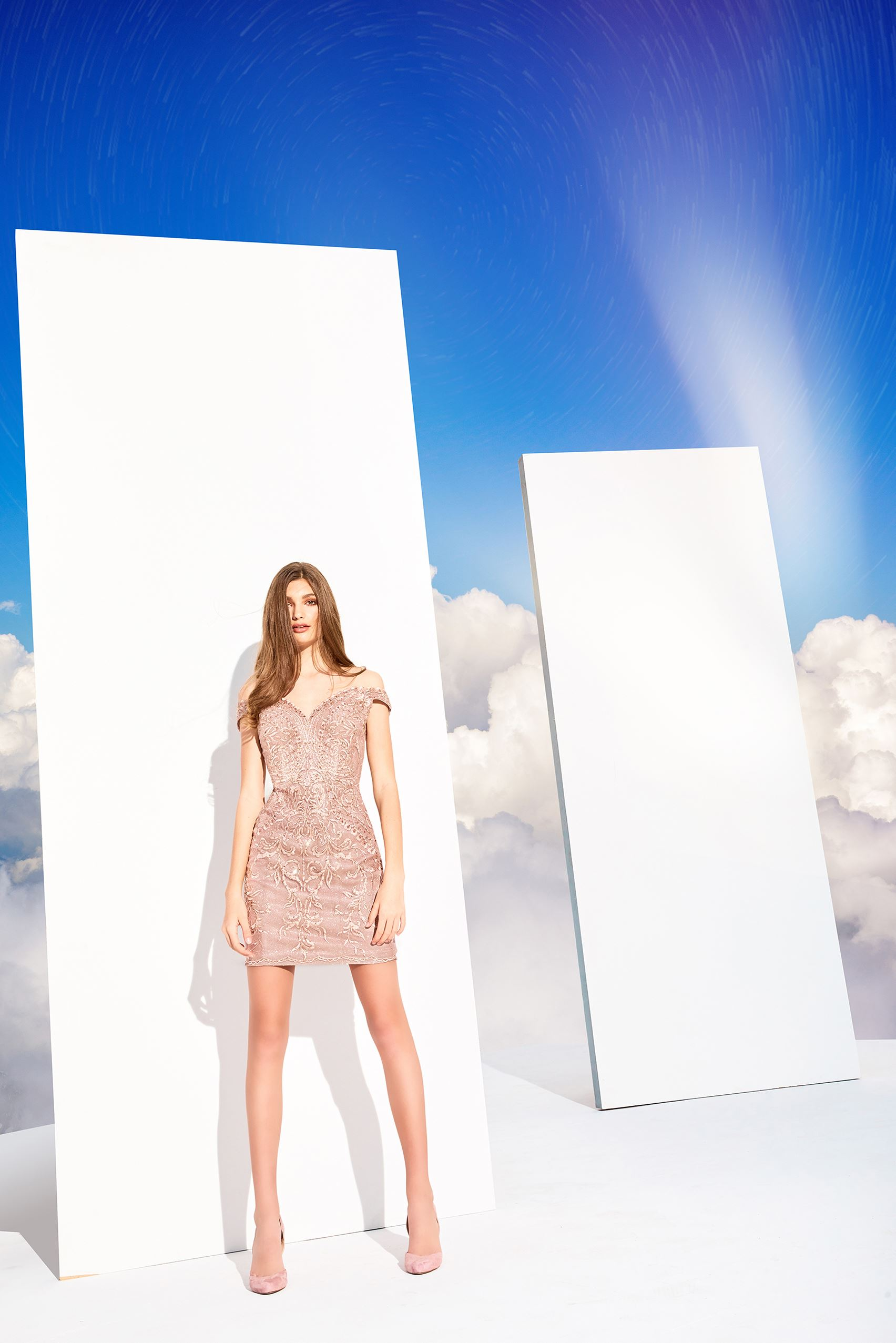 Brunette model in short champagne dress in front of clouds