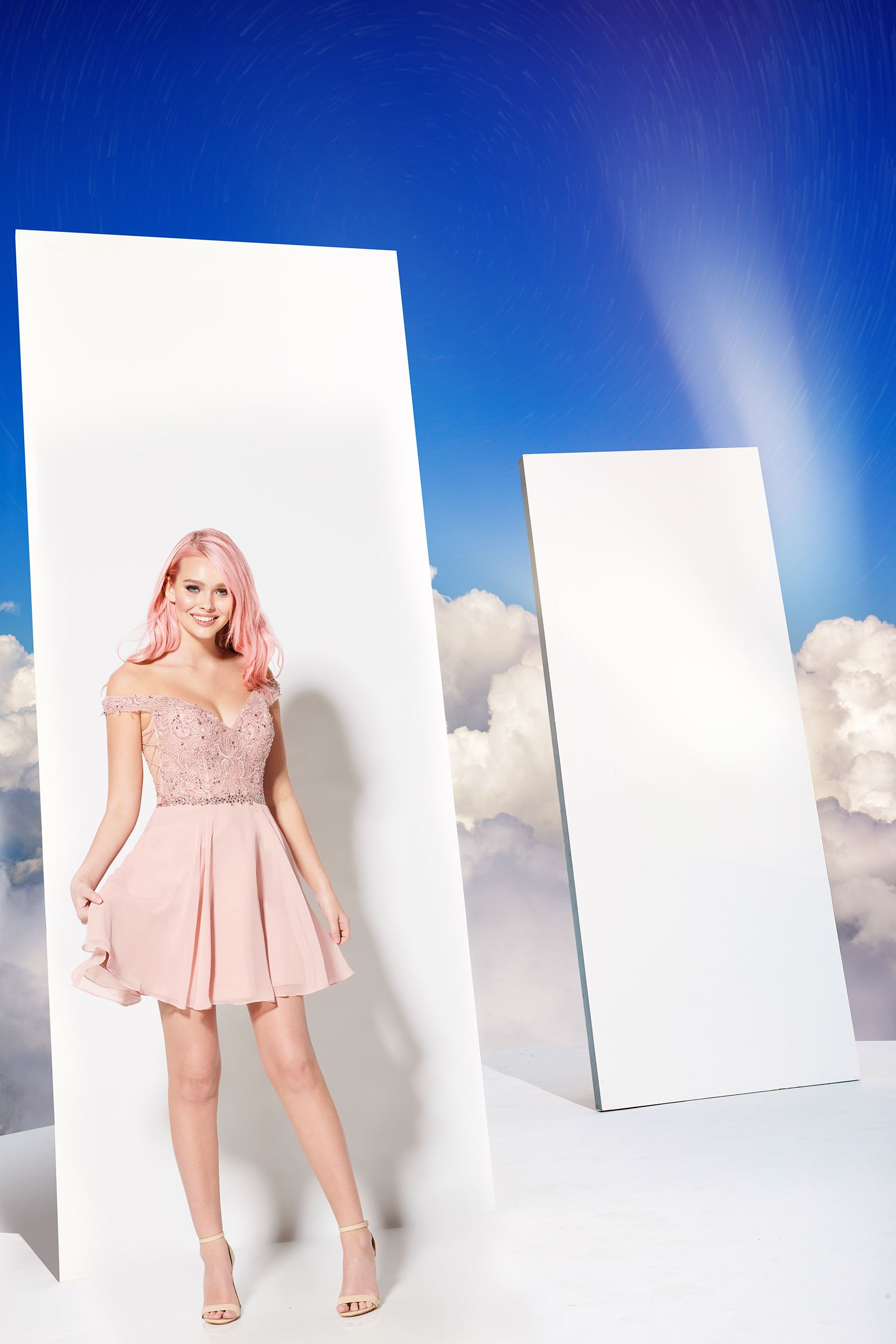 Model with pink hair in short pink dress in front of clouds