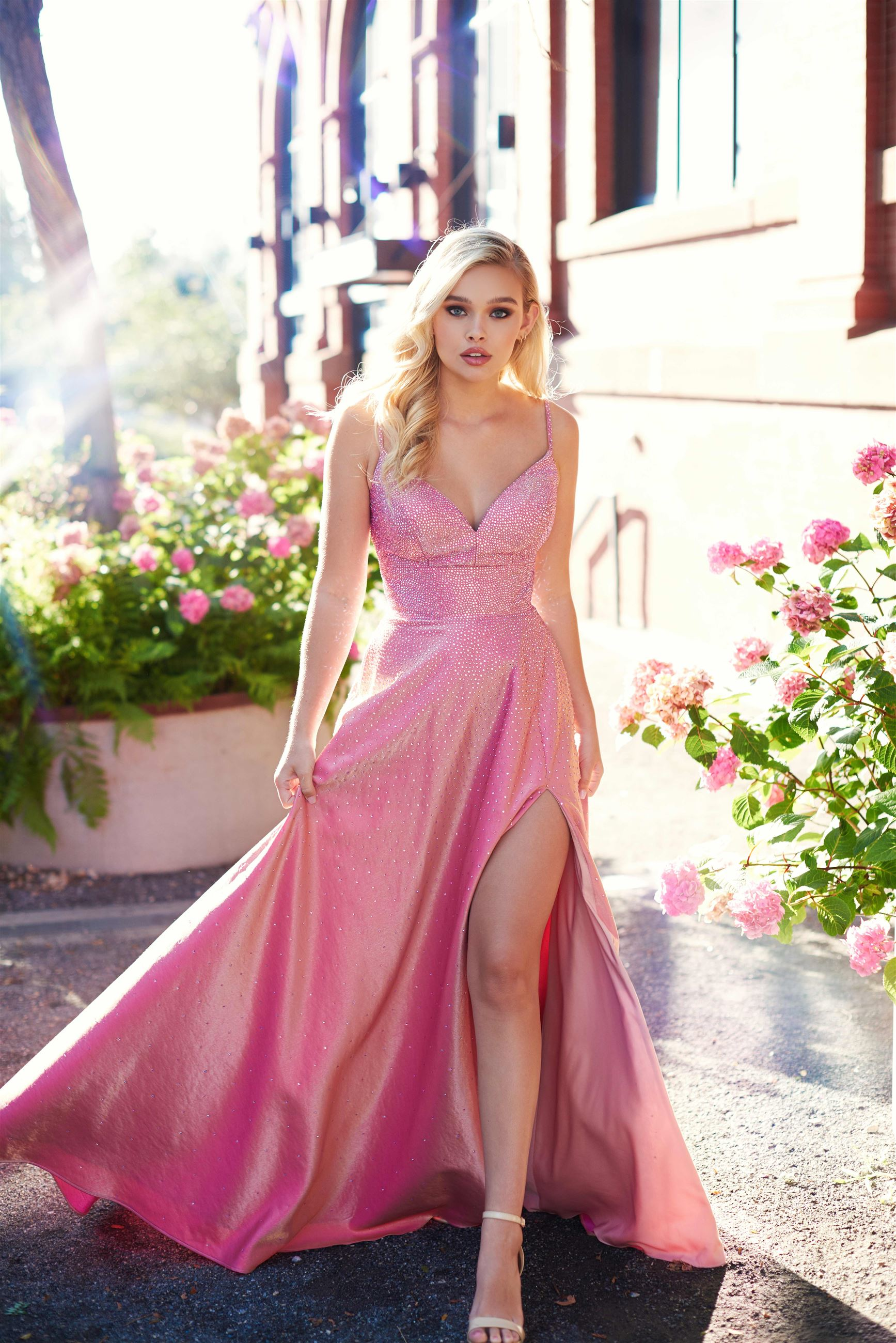 Blonde model in pink prom dress with thigh high slit by Ellie Wilde