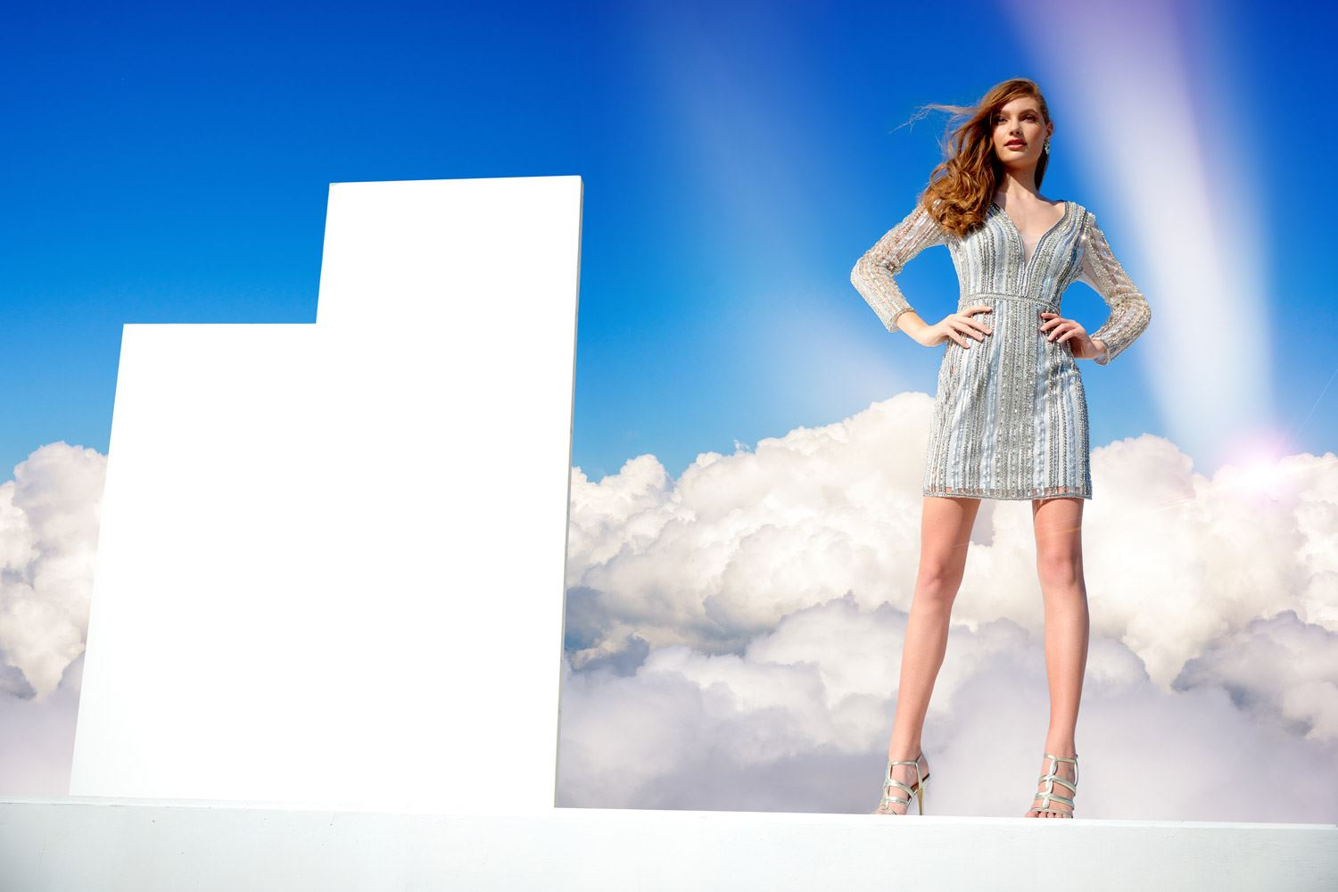 Brunette model in short silver homecoming dress in front of clouds
