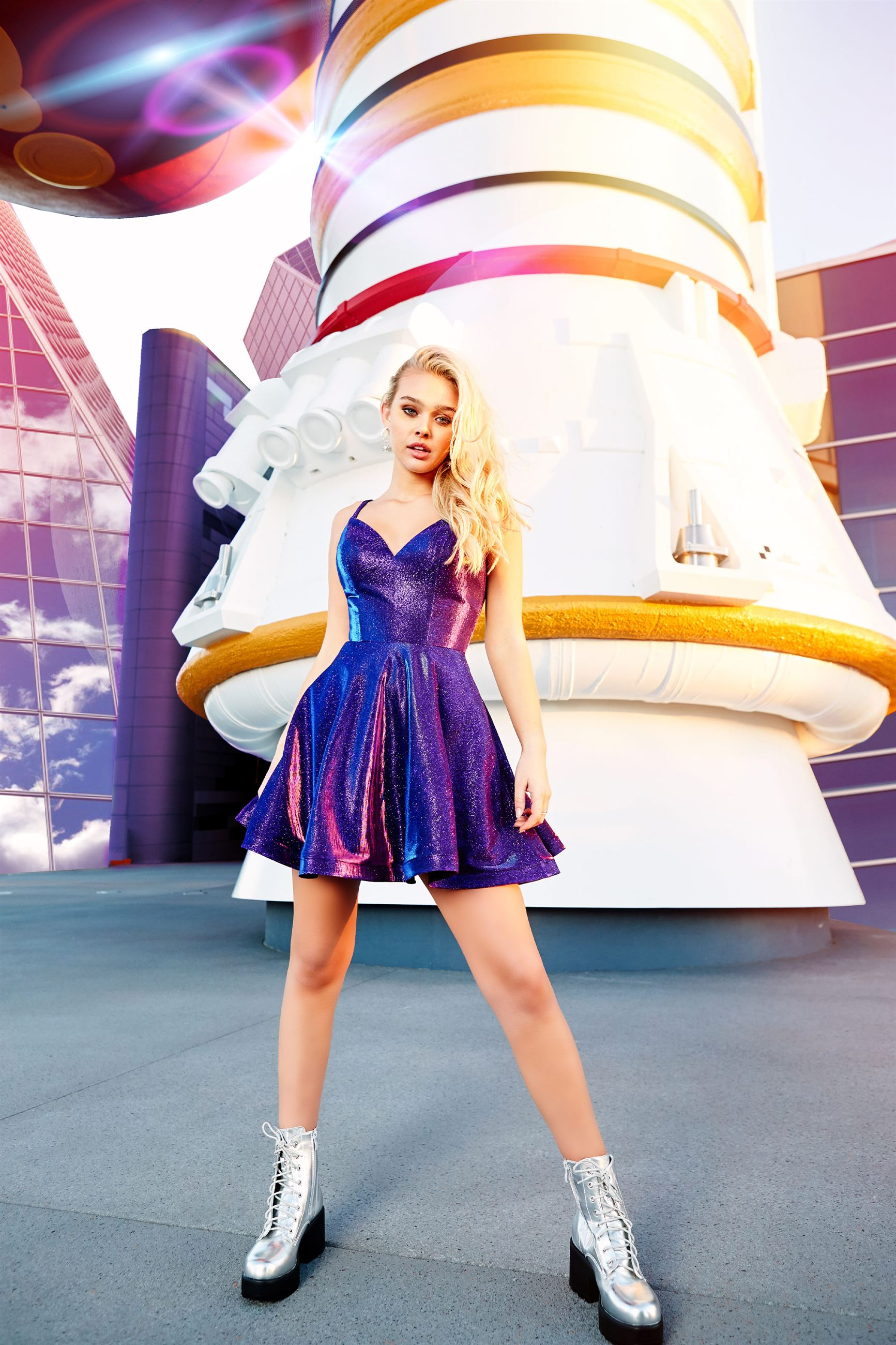Blonde model in short purple homecoming dress in front of rocket