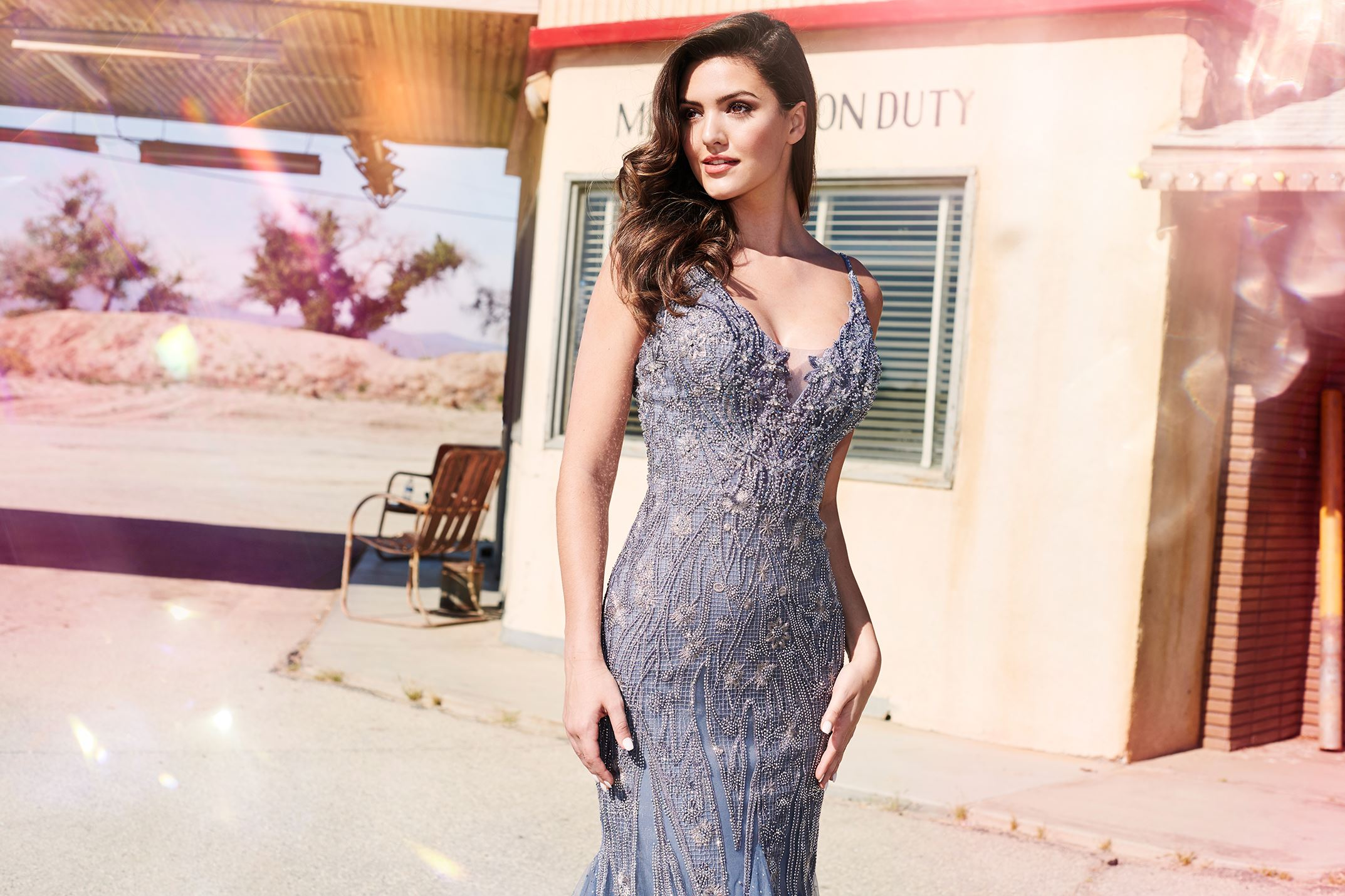Brunette model in long gray prom dress by Ellie Wilde