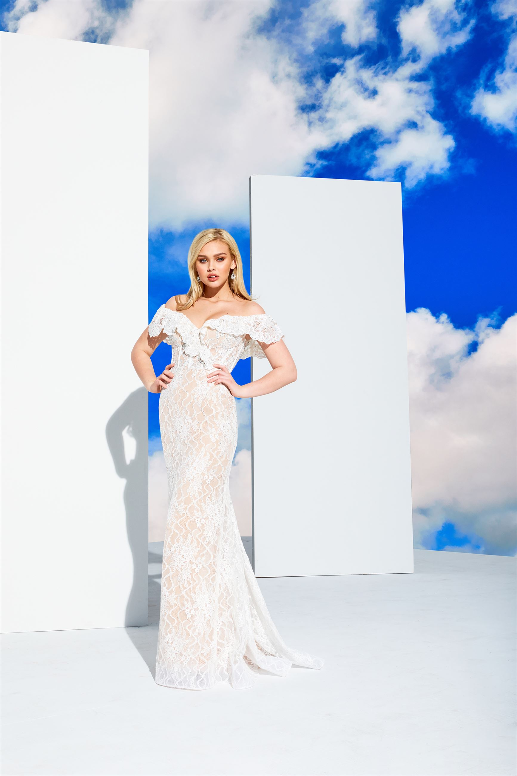 Blonde model in long white prom dress in front of clouds