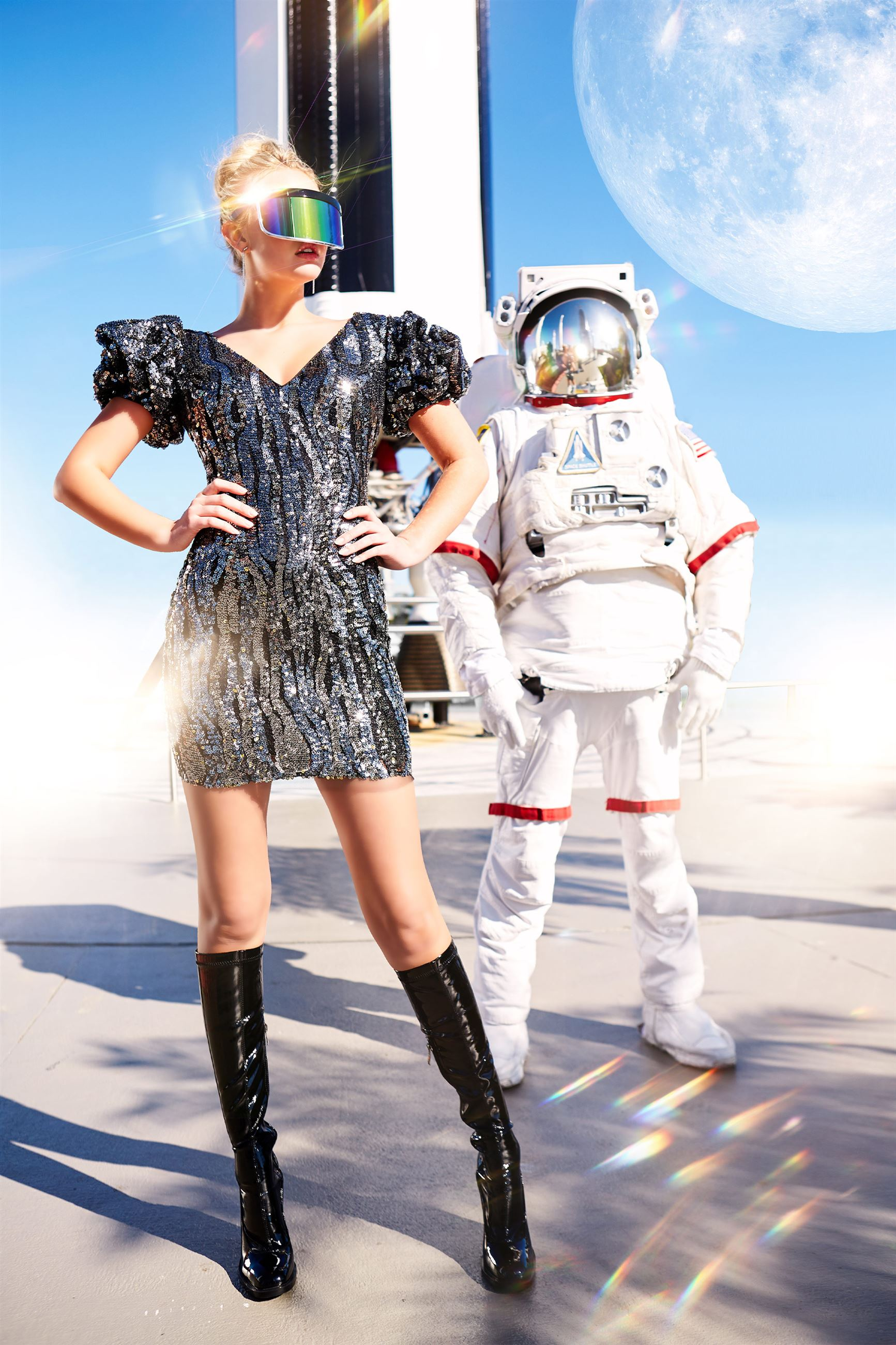 Blonde model in short black and silver dress next to astronaut